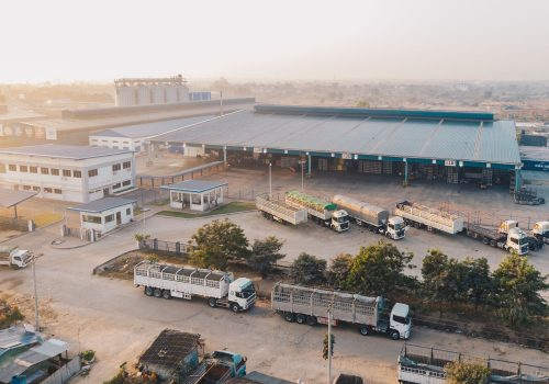 aerial-view-factory-trucks-parked-near-warehouse-daytime