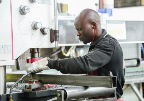 black-man-working-in-manufacturing-on-industrial-machine_t20_x60G3l