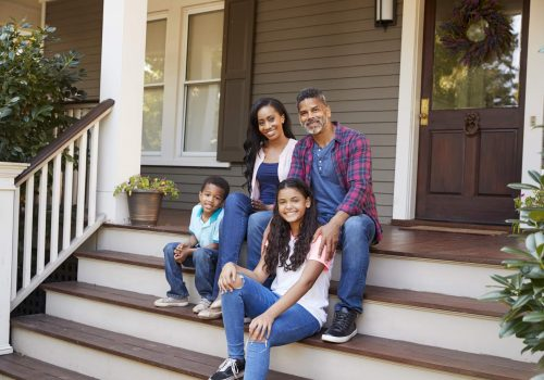 family-with-children-sit-on-steps-leading-up-to-po-PJCH5